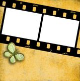 35mm film frame for two photos isolated. On a yellow wall with a butterfly Royalty Free Stock Image