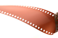 35mm film roll unfurled over white. Royalty Free Stock Photo