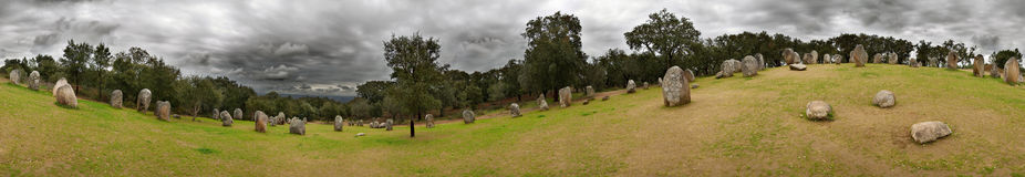 360 degrees of Almendres Cromlech. 360 degrees seamless image of Almendres Cromlech menhirs under a dark dramatic clouded sky. Evora, Portugal. Spherical royalty free stock photos