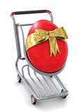 3d big red Easter egg gift in shopping cart icon. Red giant 3d Easter egg in a shopping cart - image on white background with soft shadows Royalty Free Stock Images