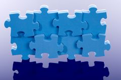 3D blue puzzle on blue background. Stock Images