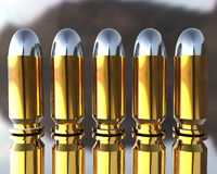 3D bullets. Bright 3D golden and silver bullets on grey Royalty Free Stock Photos