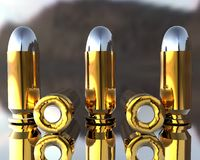 3D bullets. Bright 3D golden and silver bullets on grey Royalty Free Stock Image