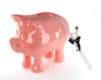 3d Businessman climbing onto a piggy bank Royalty Free Stock Photography