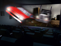 3D Cinema. In a cinema, a  3D action movie gives the impression that a truck chasing a car in the desert are taking out of the screen Royalty Free Stock Image
