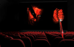 3D Cinema. A monstrous killer with a dagger menacing the spectators in a 3D cinema Royalty Free Stock Photo