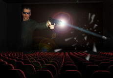 3D Cinema. Interior of a cinema. In the screen, a man is shooting with a gun. The bullet and parts of a broken glass seem to fall on the seats Stock Photography