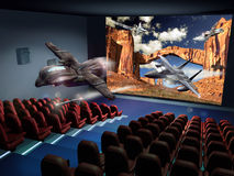 3D Cinema. Interior of a Cinema. A 3D science fiction movie. 3D effects give the sensation that a spaceship, chased by a fighter plane, is coming out of the Royalty Free Stock Photography