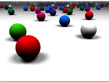 3D colored balls against white background. A bunch of 3D balls rolling in front of us created in a 3d modeling program Royalty Free Stock Photo