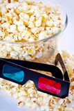 3d glasses and popcorn. 3d glasses with overflowing bowl of popcorn; movie or cinema concept with white background Royalty Free Stock Photos