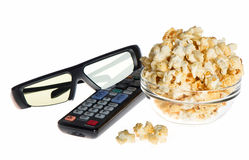 3d glasses, tv remote control and popcorn. 3d glasses, tv remote control and bowl with popcorn on white background Stock Image
