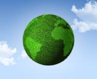 3D green grass globe on a blue sky. Grass earth globe on a blue sky - three dimensional illustration Stock Photos