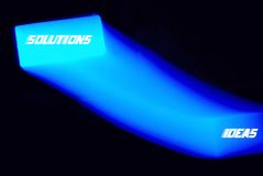 3D moving ideas/solutions sign. A glowing neon light with an ideas and solutions concept stock illustration