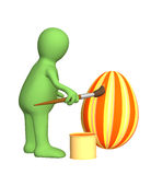3d person - puppet, painting an easter egg Royalty Free Stock Photography