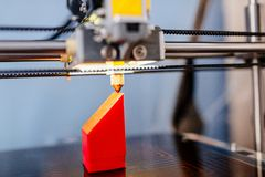 3d printer printing red plastic component. 3d printer working and printing red plastic component Royalty Free Stock Photos