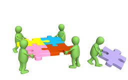 3d puppets, holding in hands a puzzle. Of multi color Royalty Free Stock Image