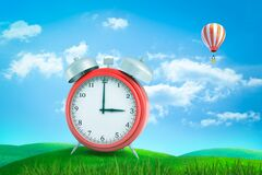 Free 3d Rendering Of Red Retro Alarm Clock Showing 3 O`clock Standing On Green Grass Under Blue Sky With Hot Air Balloon In Royalty Free Stock Photos - 169305768