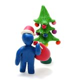 3D Santa Carrying Sack. 3D Plasticine Man as Santa Claus Carying Red Sack with Christmas Gifts on his Shoulder and Green Tree Isolated on White Background Royalty Free Stock Photography