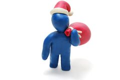 3D Santa Claus Carrying Sack. 3D Plasticine Man as Santa Claus Carying Red Sack with Christmas Gifts on his Shoulder Isolated on White Background Royalty Free Stock Photography