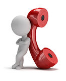 3d small people - call me. 3d small person standing next to a large handset. 3d image. White background Stock Image