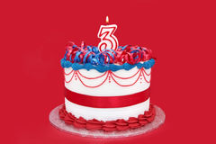 3rd Cake. Cake with numeral three candle, on vibrant red background Stock Image