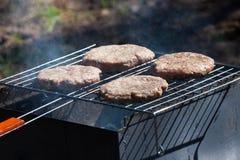4 гамбургера на решетке барбекю Стоковые Изображения