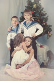 4 дет сидят вокруг рождественской елки Стоковые Изображения