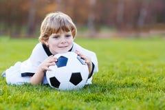 Белокурый мальчик играя футбола 4 с футболом на футбольном поле Стоковая Фотография