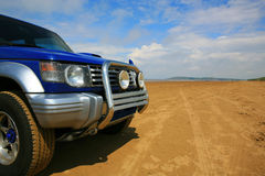 4 x 4 on deserted beach. With tyre tracks stock image