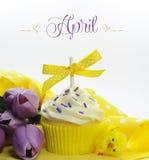 与季节性花郁金香和装饰的美好的黄色春天或复活节题材杯形蛋糕4月 库存照片