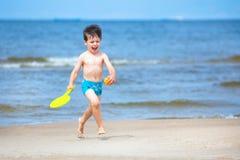 4 années mignonnes de garçon exécutant sur la plage tropicale Images stock