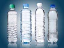 4 bouteilles d'eau sur le bleu Image libre de droits