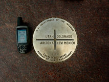 4 Corners Benchmark. GPS unit sitting next to the Brass benchmark location of the 4 corners, Utah, Colorade, Arizona, New Mexico. Concrete background royalty free stock photography