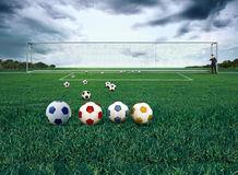 4 different colored soccer balls on a field Stock Images