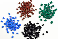 4 dyed polymer resins. Blue, brown, black, and green heaps of polymer resin for injection moulding in laboratory Stock Images