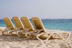 4 empty loungers. On a tropical beach (Punta Cana, Dominican Republic royalty free stock photography
