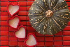4 hearts for the pumpkin!. Queensland blue pumpkin shown with four heart shaped candles on red bamboo placemat Royalty Free Stock Image