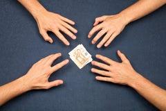 4 mãos e um wad dos euro foto de stock