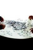 4 manos que hacen un rompecabezas Imagen de archivo