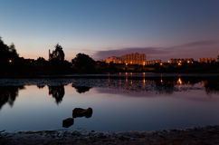 4 minutes of the June Night. Scenic view of silhouetted lake with stones at sunrise with lights of city buildings in background. 215 seconds exposure Royalty Free Stock Image