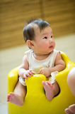 4 month old Asian baby girl having a haircut. While sitting in a yellow chair Stock Photo