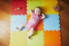 Free 4 Months Old Baby Girl Lying On Colorful Play Mat Stock Images - 149457474