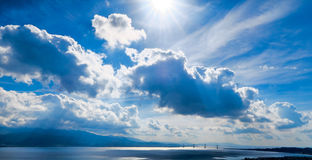 4 People on Body of Water Under Blue Sky and White Clouds Royalty Free Stock Image