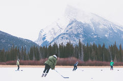 4 People Playing Hockey Outside Near Brown and Green Trees Royalty Free Stock Photo