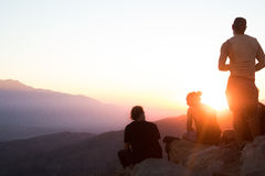 4 People Sitting on Rocks on Hill Against Setting Sun Royalty Free Stock Photo
