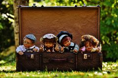 4 Porcelain Dolls in Brown Rectangular Box Royalty Free Stock Photo