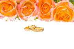 4 rosas e anéis de casamento amarelos vermelhos sobre o branco Foto de Stock Royalty Free