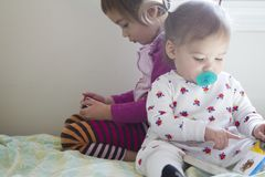 Free 4-year-old Girl Watching Cell Phone And 1-year-old Girl Reading Book Stock Photo - 141718660