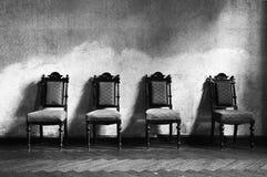 4 zwarte stoelen/wit stock afbeelding