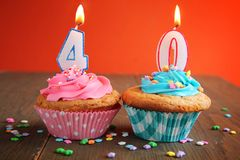 40 birthday cupcake. Number forty birthday candles on a blue and pink cupcake on a orange background Stock Image